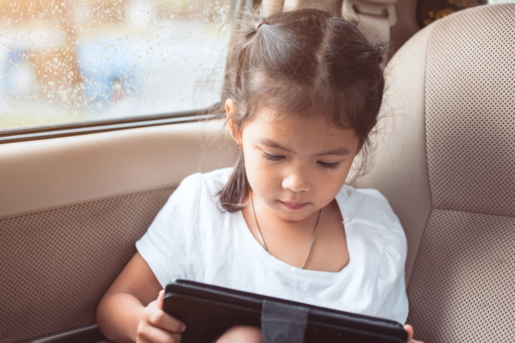 child reading tablet in car