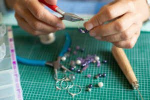 person making homemade jewelry