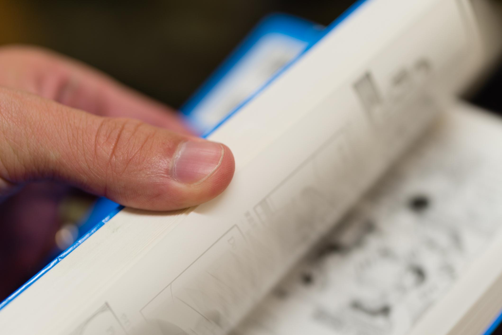 person flipping through a graphic novel