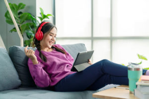 teen girl using a tablet and wearing headphones