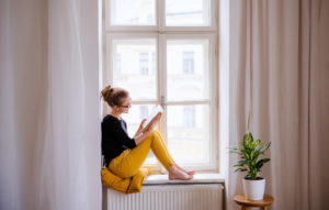 Teen or Young Adult Reading in a Window