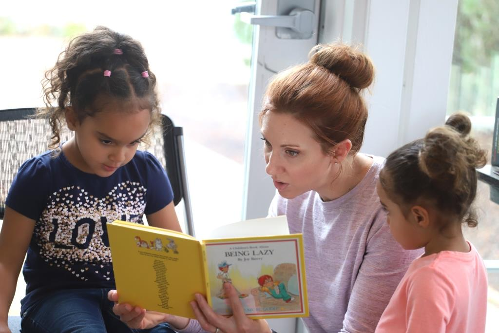 woman reading to girls