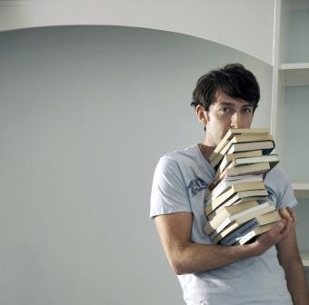 Man balancing big stack of books with one hand