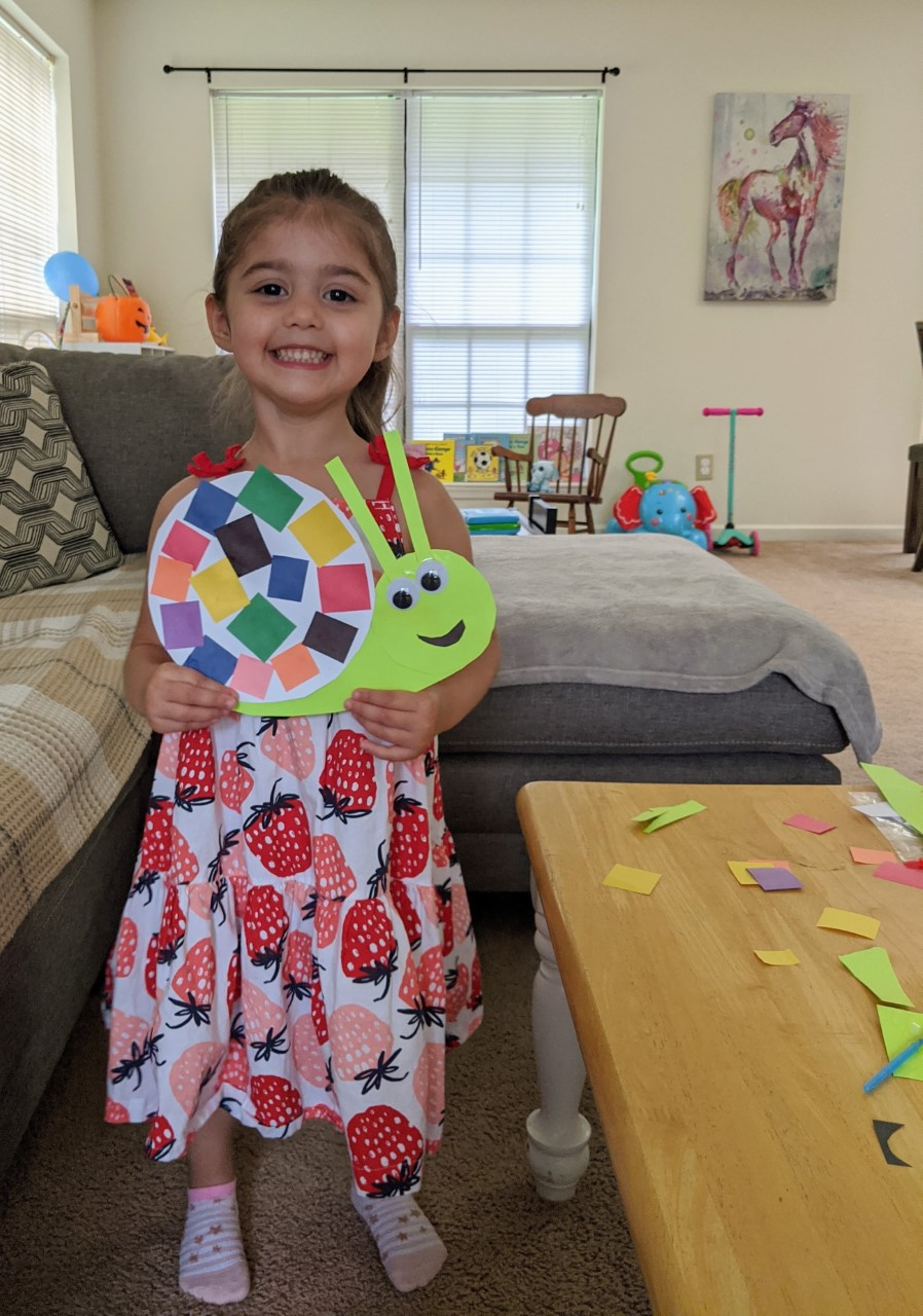 little girl with snail craft