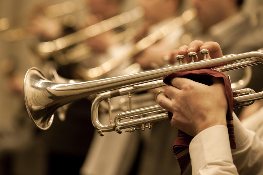 close up of hands playing a trumpet in a concert band